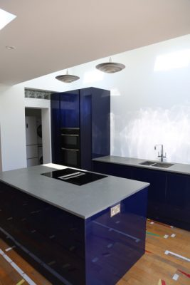 The kitchen island in the center and kitchen appliances either side